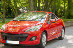 A young girl with a red car Stock Image