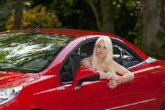 A young girl with a red car Royalty Free Stock Image