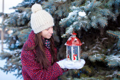 Young girl with red Christmas lantern in the snow Stock Image