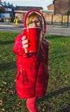 Young girl in red clothes holding red plastic cup forward-healthy lifestyle concept - Image. Young activate blonde girl in red clothes standing on a street and royalty free stock image