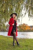 A girl in a red coat and hat stands under the branches of a willow on the bank of the river of the lake Royalty Free Stock Photography
