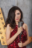 Young girl in red cocktail dress singing with microphone Stock Photos