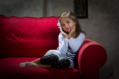 Young girl of red couch royalty free stock photography