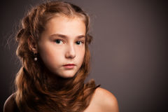 A young girl with red curly hair Stock Image