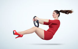 Young girl in a red dress with a car steering wheel Stock Images