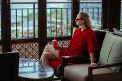 A young girl in a red dress is drinking a red cocktail in the lobby of the hotel. A blonde woman in sunglasses is stock image