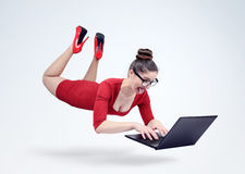 Young girl in a red dress and glasses hovering in the air with a laptop. Stock Photo
