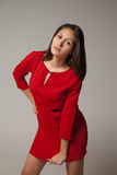 Young girl in red dress on gray background Royalty Free Stock Images