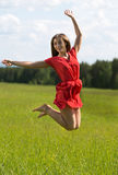 Young girl in a red dress jumping in a field coniferous forest Royalty Free Stock Photo