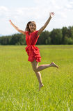 Young girl in a red dress jumping in a field with forest Stock Photo