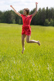 Young girl in a red dress jumping in a field Stock Photos