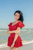 Young girl in red dress on the sea Royalty Free Stock Photo