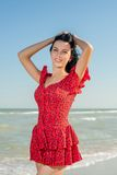 Young girl in red dress on the sea Royalty Free Stock Photos