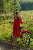 A young girl in a red dress is standing near a bicycle with a red umbrella. In the background there is a forest Stock Photography