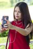 Young girl in red dress taking a selfie Royalty Free Stock Photography