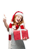 Young girl with red gift showing thumbs-up. Young red-haired girl in santa hat with red gift looking at camera with nice toothy smile and showing thumb-up Royalty Free Stock Photo
