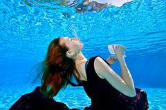 A young girl with red hair in a beautiful dress is swimming underwater in the pool on a blue background. royalty free stock photos