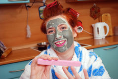 The young girl with red hair in hair curlers with a clay face pack in kitchen does manicure Royalty Free Stock Photo