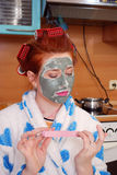 The young girl with red hair in hair curlers with a clay face pack in kitchen does manicure Stock Photos