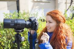 Young girl with red hair photographing on the street. stock images