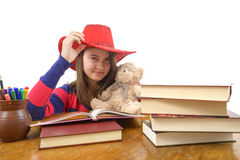 Young girl with red hat and her teddy bear at the table Royalty Free Stock Images