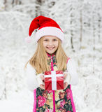 Young girl with red hat holds out a gift Stock Photo
