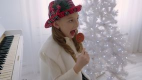 Young girl in red hat licking lollipop near white piano and Christmas tree stock video