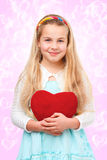 Young girl with a red heart Stock Image
