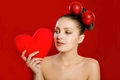 Young girl with a red heart toy in  hands Royalty Free Stock Photos