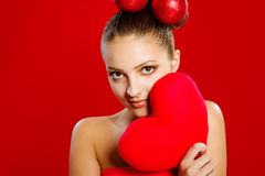 A young girl with a red heart toy Royalty Free Stock Images