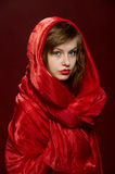 Young girl in a red hood. Attractiv young girl fashion portrait with magnetic red head covering in studio Stock Photography