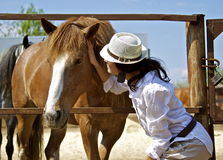 Young girl with the red horse. Young woman in a white shirt talking to the red horse Royalty Free Stock Images