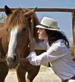 Young girl with the red horse. Young smiling woman in a white shirt talking to the red horse Stock Photography