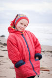 The young girl in a red jacket. On the beach stock photo