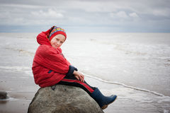 The young girl in a red jacket. On the beach royalty free stock photography