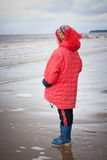 The young girl in a red jacket. On the beach royalty free stock photo