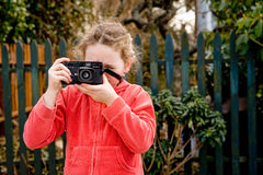 Young girl in red jacket with camera. Young girl taking photo towards camera, fence behind Royalty Free Stock Photography