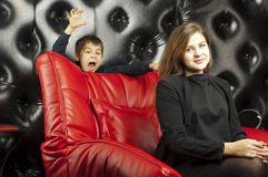 Young girl on a red leather sofa Stock Photography