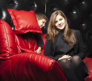 Young girl on a red leather sofa Royalty Free Stock Photography