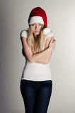 Young girl in a red santa hat frezing Stock Photos
