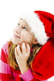 Young girl in red Santa hat, looking up Stock Photos
