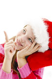 Young girl in red Santa hat, looking up and pointing copy space Royalty Free Stock Photos