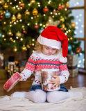 Young girl in red santa hat opening Christmas gifts Royalty Free Stock Images
