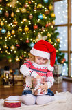Young girl in red santa hat opening Christmas gifts Royalty Free Stock Photography