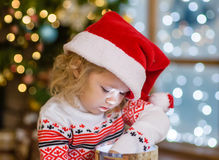 Young girl in red santa hat opening Christmas gifts Royalty Free Stock Photo