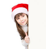 Young girl in red santa hat standing behind white board and showing thumbs up.  on white Stock Photography