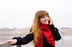Young girl in the red scarf calling on phone Stock Photography