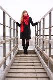 Young girl in the red scarf standing on stairs Royalty Free Stock Photos