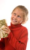 Young girl in red shaking gold Christmas present Royalty Free Stock Image
