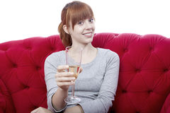 Young girl on red sofa cheers with you Stock Photography